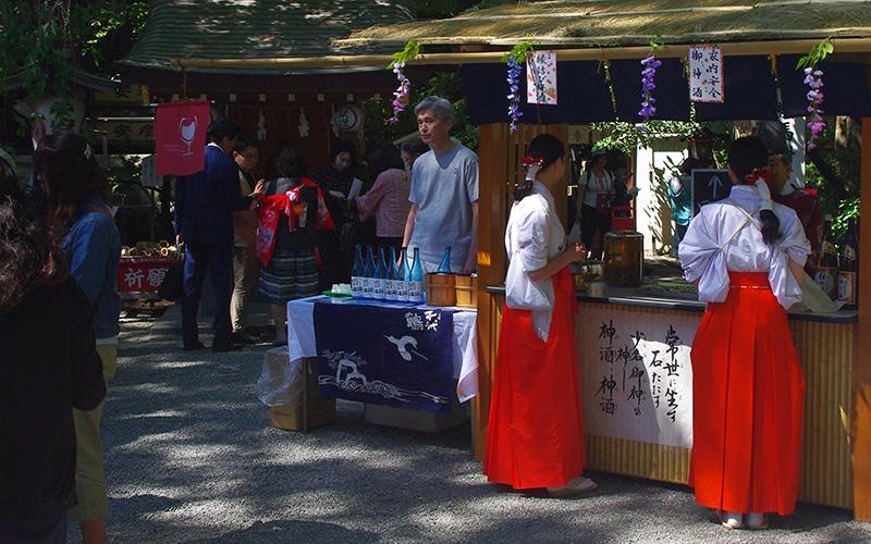 子安神社境内で、日本酒を振る舞う巫女さんの様子